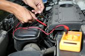 stock photo of voltage  - Auto mechanic uses multimeter voltmeter to check voltage level in car battery - JPG