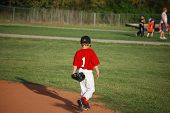 stock photo of hitter  - Little league youth baseball player walking on field - JPG