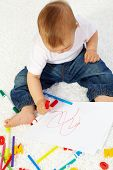 Image of cute little boy drawing with crayons