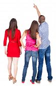 Back view of three friends. pointing man and two women looking. Rear view people collection.  backsi