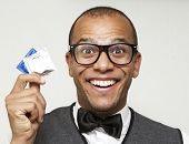 stock photo of condom  - Nerdy looking mixed race male holding some condoms with a humorous expression - JPG