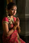 Young Indian female in traditional sari dress praying in a hindu temple.
