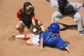 image of umpire  - Softball player sliding into home plate while umpire rules safe - JPG