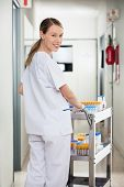 Portrait of happy young female lab technician pushing medical cart in corridor