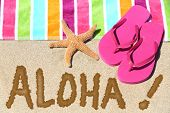Hawaii beach travel concept. ALOHA text written in sand with water next to beach towel and summer sa