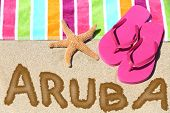 Aruba beach travel concept. ARUBA written in sand with water next to beach towel, summer sandals and