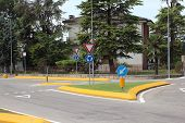 Roundabout With Yellow Curb And Green Grass In Summer