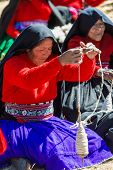 PUNO, PERU - JULY 25, 2013: woman weaving in the peruvian Andes at Taquile Island
