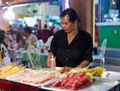 BANGKOK, THAILAND - JANUARY 9, 2012: Man prepares traditional Thai food on Khao San Road food stall.