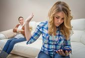 image of disappointment  - Teenage daughter looking at messages in a smartphone and ignoring her furious mother - JPG