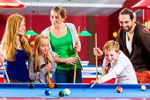 Family playing together billiard with queue and balls on pool table