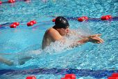 Swimmer in cap breathing performing the breaststroke - right profile