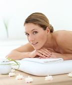 Beautiful middle-aged woman relaxing on massage bed