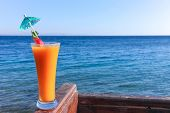Long drink glass with a cocktail umbrella, garnished with strawberry against Red Sea in the Sinai region of Egypt