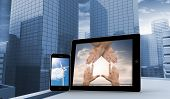 Hands and wind turbine on smartphone and tablet screens against view of dull cityscape
