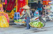 HANOI, VIETNAM, JANUARY 13, 2013 - a seller of fruits sells her merchandise on the street