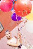 Beautiful Lady In Retro Outfit Holding A Bunch Of Balloons Between Old Buildings
