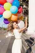 Beautiful Lady In Retro Outfit Holding A Bunch Of Balloons On The Street