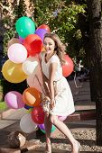 Beautiful Lady In Retro Outfit Holding A Bunch Of Balloons In City Park