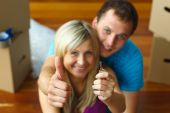Couple Holding A Key With Thumbs Up. Buying New House