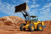 stock photo of earth-mover  - wheel loader bulldozer with fully raised bucket over blue cloudy sky standing in sandpit - JPG
