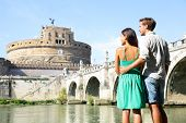 Rome travel tourists by Castel Sant'Angelo. Happy romantic couple looking at the roman castle enjoyi