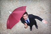 Businessman under umbrella looking worried to the sky and checking if it's raining