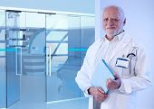 Old doctor standing in front of MRI room at hospital, holding tablet, smiling.