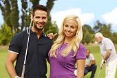 Attractive young couple standing and embracing at golf course.