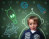 Imagination and dreams of a child, dressed as a space man in front of a blackboard with chalk drawin