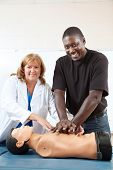 Adult first aid or EMT student practicing CPR on a dummy, with the help of a doctor or nurse.  Verti