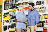 Happy father with son checking list in hardware store