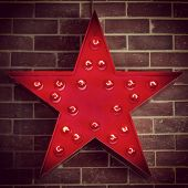 Red Star Sign with Light Bulbs on a Brick Background