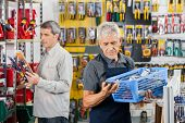 Senior salesman working at hardware store with customer in background