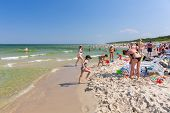 JASTARNIA, POLAND - 3 august 2014: People on the sunny beach of Baltic Sea in Jastarnia. Jastarnia is very popular tourist destination for summer holidays at Baltic Sea in Poland.