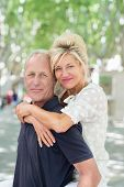image of she-male  - Middle-aged man giving an attractive smiling woman a piggy back ride as she hugs him around the shoulders on a hot summer day in town