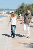 Couple Walking Hand In Hand Along The Waterfront