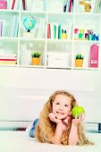 Cute joyful girl lying on a floor at home and and eating fresh apple.