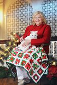 A senior woman happily holding her white cat in a room decorated for Christmas.