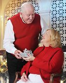 A senior man happily handing a gift to his wife in a Christmas-decorated room.