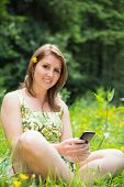 Portrait of a relaxed young woman text messaging in field