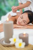 Beautiful brunette enjoying a herbal compress massage at a luxury spa