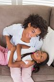 Pretty mother sitting on the couch tickling daughter at home in the living room