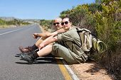 Hiking couple sitting on the side of the road smiling at camera on a sunny day