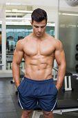 Shirtless muscular man looking down in gym