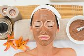 Smiling brunette getting a mud treatment facial in the health spa