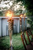 pic of tiki  - Burning Tiki Torch In The Backyard Close Up - JPG