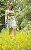 Cute young woman standing in field against the trees