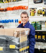 Portrait of mature worker with tool package in hardware shop