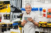 Portrait of happy senior customer holding digital tablet in hardware store